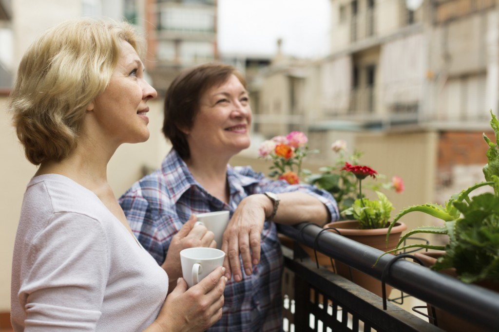 Old women on balcony with coffee